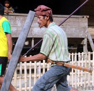 Sado Taringolu memegang tombak dan perisai. Guma terikat di pinggang. Foto: Budi-Karsa Institute.