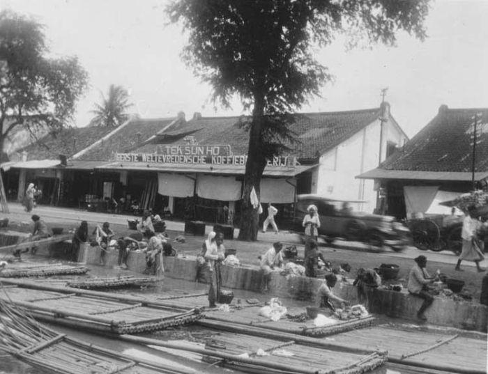 Mencuci pakaian di sepanjang Molenvliet, Batavia. Di latar belakang tampak Tek Sun Ho. 1932. (Dok. Troppenmuseum)
